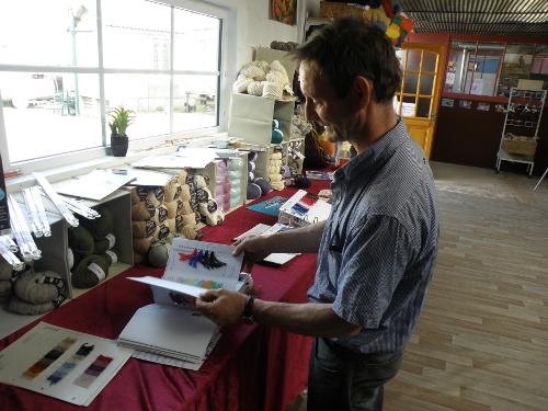 Dominique Pecut consulte un catalogue d'échantillons de laines