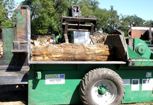Un tronçon de bois est déposé sur le plateau de la fendeuse